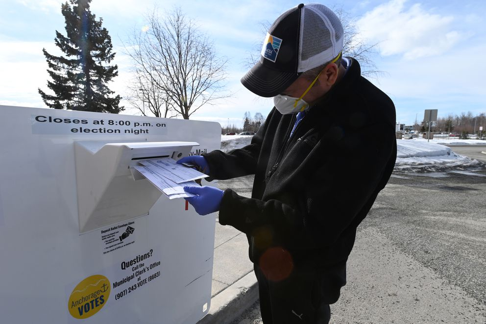 Jason Baer places a ballot in a secure Vote-By-Mail Ballot Drop Box at the Loussac Library on Monday, April 6, 2020. Tuesday is Election Day for the Regular Municipal Election. Baer wore a mask and gloves as a precaution while running errands. (Bill Roth / ADN)