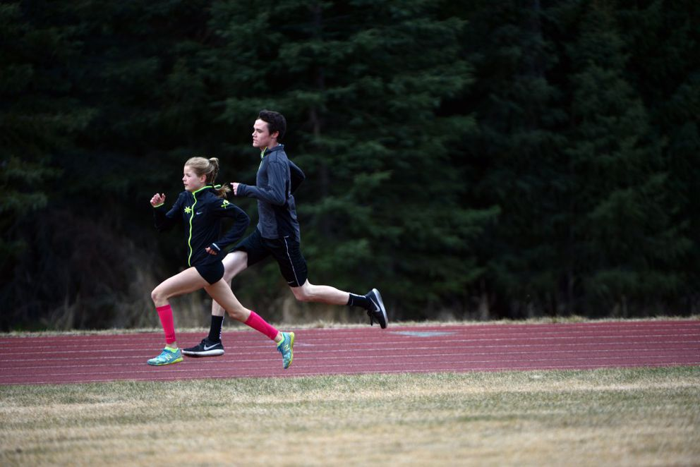Long-time friends and teammates Allie Ostrander, left, and Jonah Theisen sprint during interval training on at the Skyview Middle School track last year.(Erik Hill/Alaska Dispatch News)