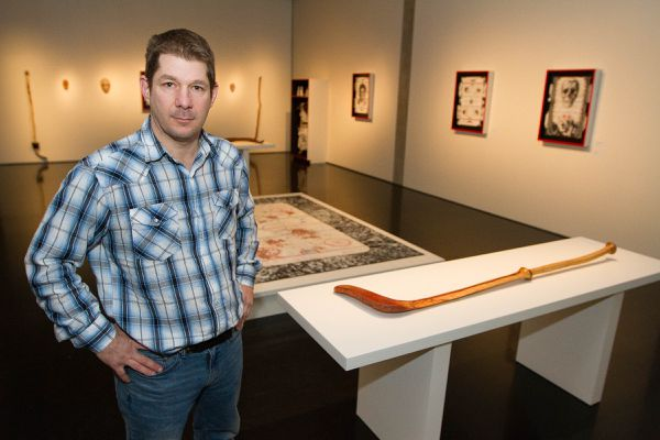 UAA art faculty Mike Conti poses for a photo in his exhibit, Puck and Stick, at the Anchorage Museum in Anchorage, Alaska Wednesday, Feb. 10, 2016.