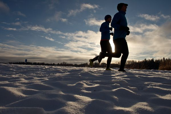 Two runners pass Westchester Lagoon at midday on November 16, 2017. (Marc Lester / Alaska Dispatch News)