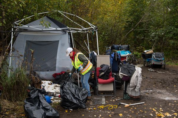 Nicole Limberg of Anchorage Parks and Recreation sorts through items at a camp near Spenard Road and the Chester Creek greenbelt on September 21, 2018. City officials began a pilot program to clean up homeless camps in three days, while allowing evicted campers to store their belongings for 30 days at Central Transfer Station. (Marc Lester / ADN)