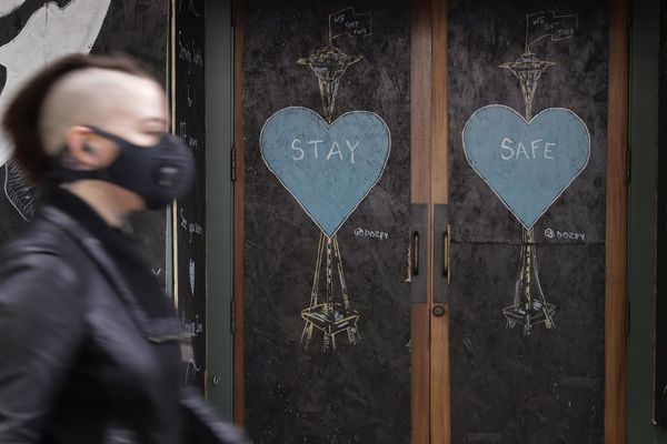A pedestrian wearing a face mask walks past art by the street artist @dozfy, featuring the Space Needle on the boarded-up Virginia Inn Restaurant and Bar, Saturday, May 16, 2020, in downtown Seattle. On Saturday, officials reported that Washington state had reached the grim milestone of 1,000 deaths from the coronavirus. (AP Photo/Ted S. Warren)