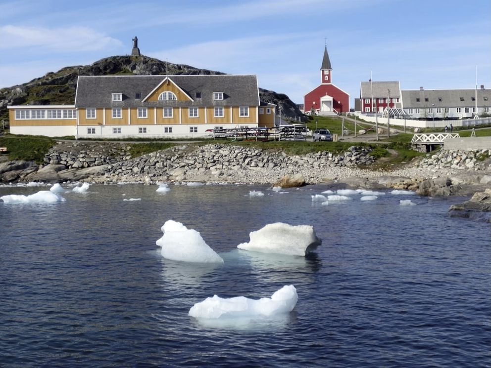 In this image taken on June 13, 2019 small pieces of ice float in the water off the shore in Nuuk, Greenland. Milder weather than normal since the start of summer in Greenland, led to the UN's weather agency voicing concern that the hot air which produced the recent extreme heat wave in Europe could be headed toward Greenland where it could contribute to increased melting of ice. (AP Photo/Keith Virgo)