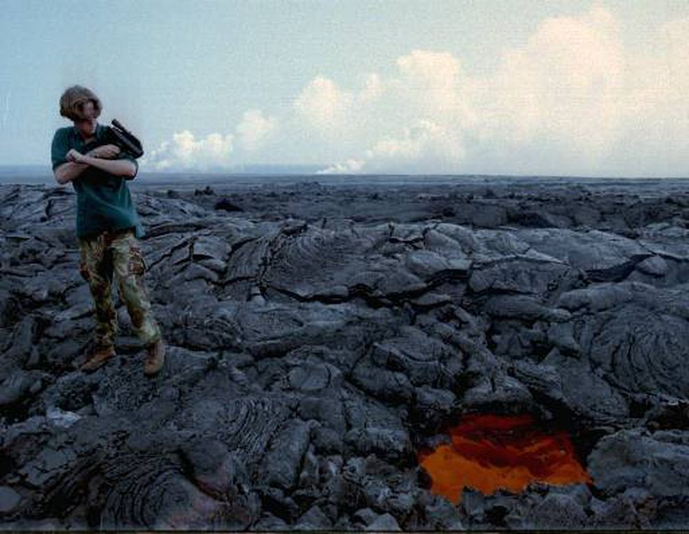 Volunteer Rich Krahenbuhl uses a radar gun to measure the speed of lava running through a lava tube Nov. 20, 1997, at the east edge of Hawaii Volcanoes National Park on the island of Hawaii. (AP Photo/Tony Cheng, File)
