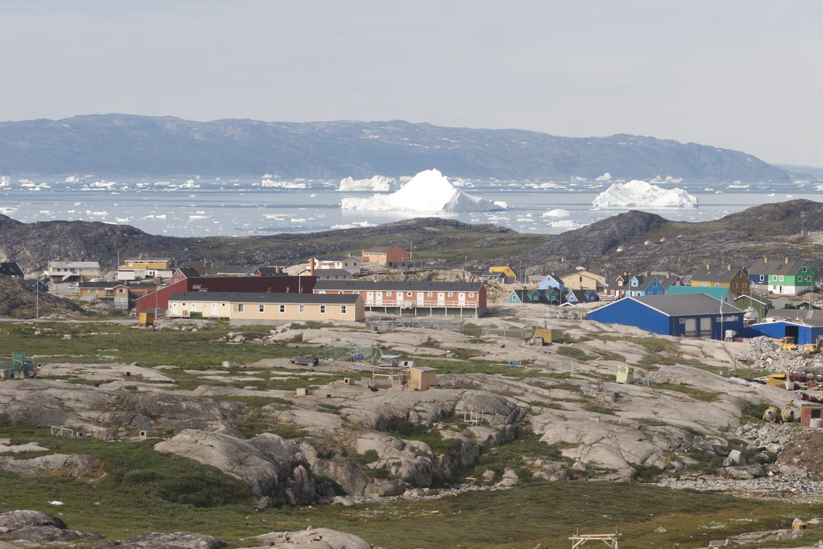 The brightly painted houses of Ilulissat, Greenland, stand in stark contrast to the green-and-gray tundra and bright white icebergs floating in the adjacent bay. (Dave Levinthal/Dallas Morning News/MCT)