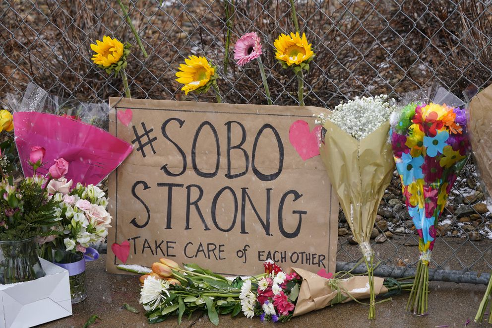 A sign from residents of south Boulder stands amid bouquets left along a fence put up around the parking lot where a mass shooting took place in a King Soopers grocery store Tuesday, March 23, 2021, in Boulder, Colo. (AP Photo/David Zalubowski)