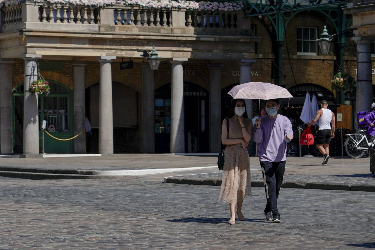 A couple wear face masks as they shelter from the sun under an umbrella, while they walk in Covent Garden, in London, Monday, June 14, 2021. British Prime Minister Boris Johnson confirmed Monday that the next planned relaxation of coronavirus restrictions in England will be delayed as a result of the spread of the delta variant first identified in India. (AP Photo/Alberto Pezzali)