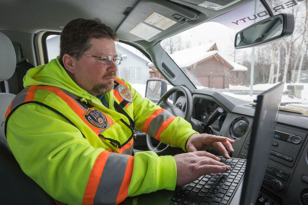 John Snelson, the Municipality of Anchorage's right-of-way enforcement lead, writes a citation on Tuesday. (Loren Holmes / Alaska Dispatch News)