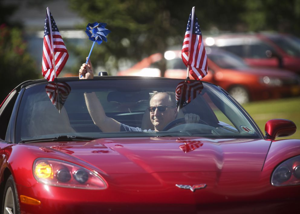 A member of the Anchorage Corvette Association waves to residents as he drives in a parade to celebrate seniors living at Chugach View and Chugach Manor. (Emily Mesner / ADN)