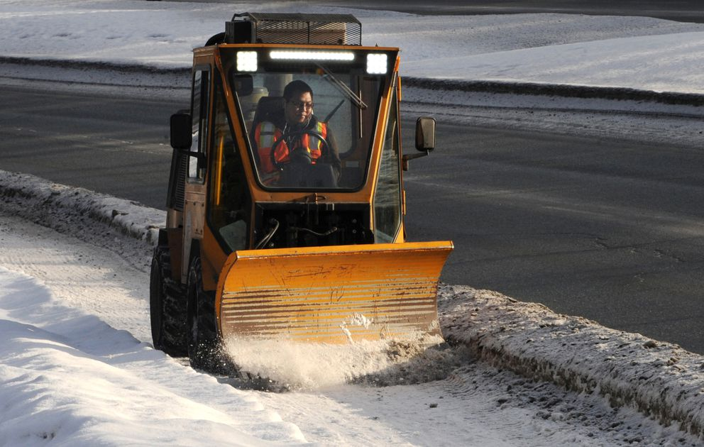 Nels Jasper with the city's street maintenance department scraped the icy sidewalk along Northern Lights Boulevard with a special blade on Thursday, Jan. 31, 2019. (Bill Roth / ADN)