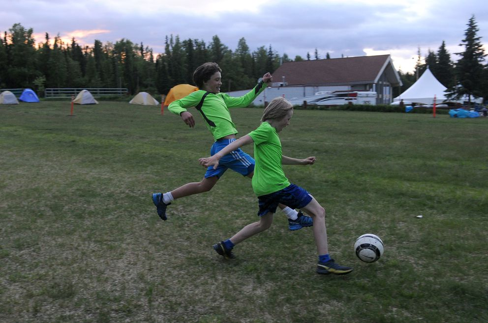 Carter Brubaker and Dylan Amy play soccer during a break at the Midnight Sun Ski Jump-A-Thon. (Bob Hallinen / ADN)