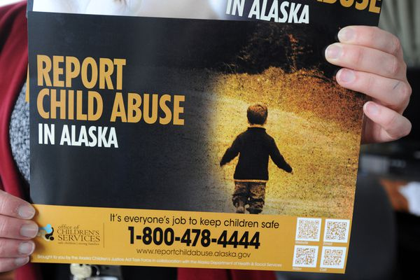 Centralized Intake Manager Lindsay Bothe holds new posters publicizing the new statewide hotline for reporting child abuse on Wednesday afternoon, August 23, 2017, at the Office of Children's Services downtown. (Erik Hill / Alaska Dispatch News)