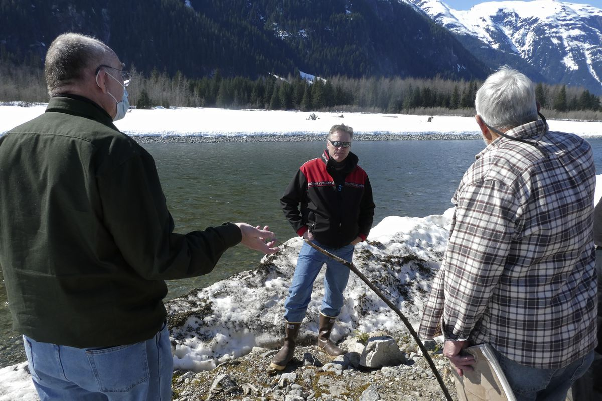 Alaska Gov. Mike Dunleavy, center, listens as residents discuss a levee they have concerns with on Thursday, April 22, 2021, in Hyder, Alaska. Hyder was among the southeast Alaska communities that Dunleavy visited as part of a one-day trip. (Becky Bohrer / Associated Press)