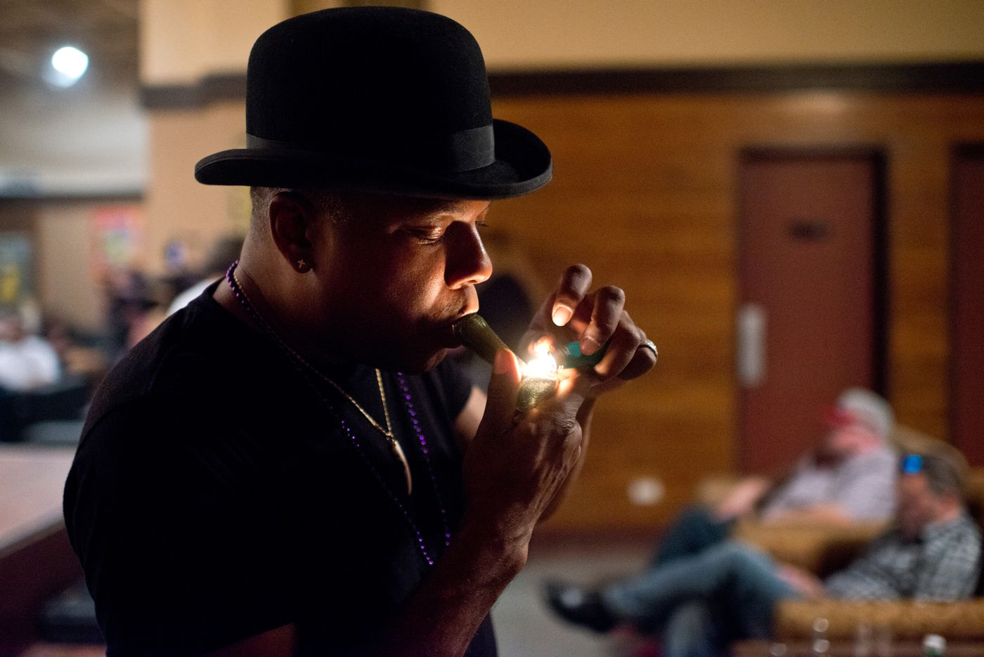 Comedian and entertainer Kelly Lee Williams smokes a pipe before the start of the comedy show he was emceeing at Pot Luck Events. Pot Luck Events hosted a comedy show at their location on 3rd Avenue in Anchorage on July 1, 2015. The club describes itself as a marijuana-friendly private club.