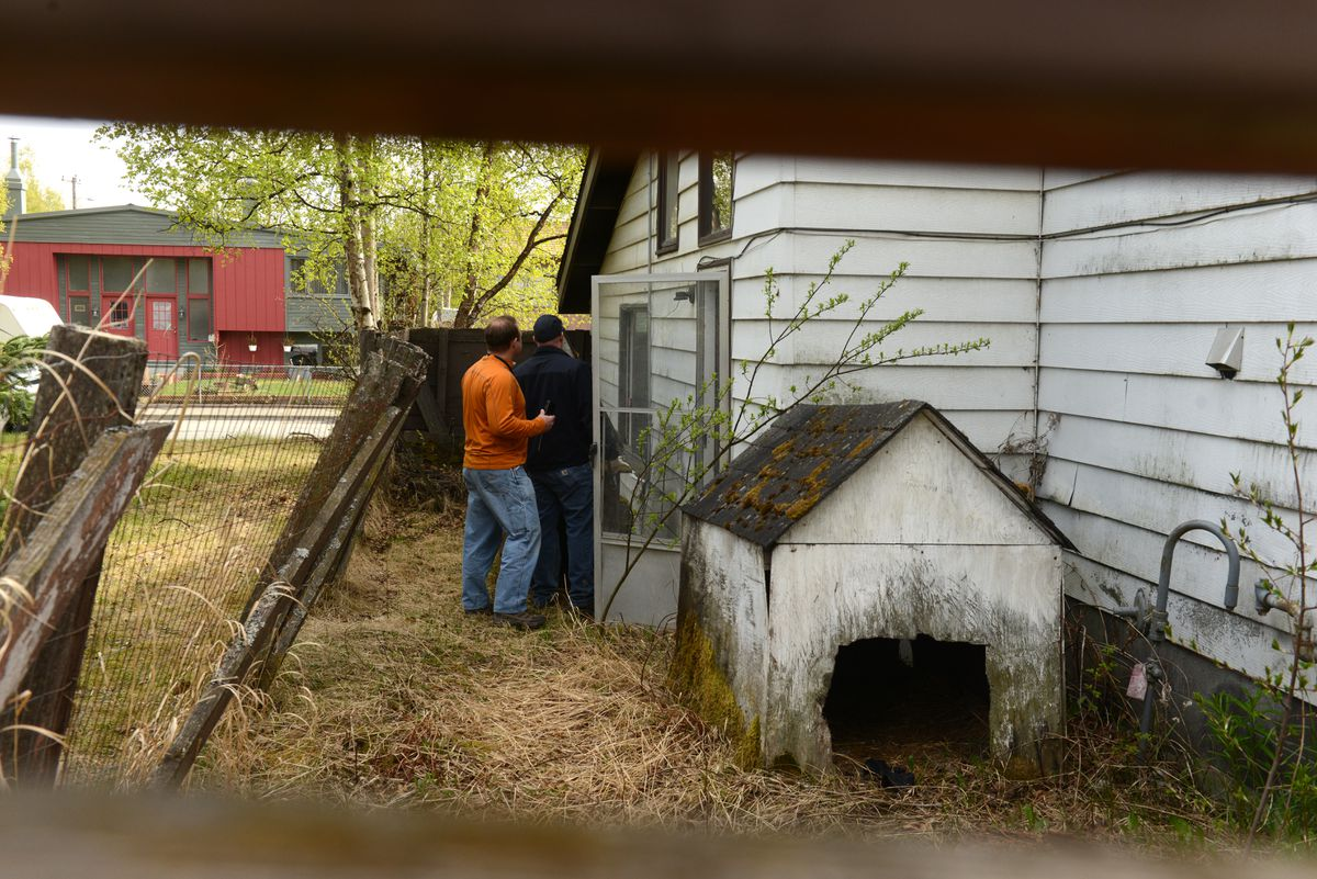 Municipality of Anchorage code enforcement officers Clark Rosencrans and William Peterson inspect the house at 1430 Columbine St. and post a notice of violation on Wednesday, May 17, 2018. A notice to vacate the structure had previously been posted. Two people illegally in the house left when the officers were there. (Bob Hallinen / ADN)