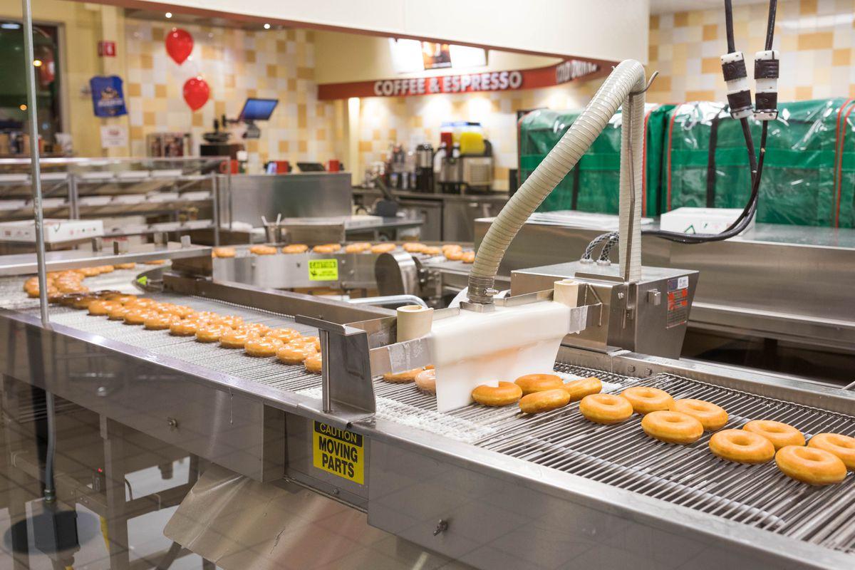 Doughnuts move along a conveyor belt at Krispy Kreme on Wednesday, Dec. 14, 2016. (Loren Holmes / Alaska Dispatch News)