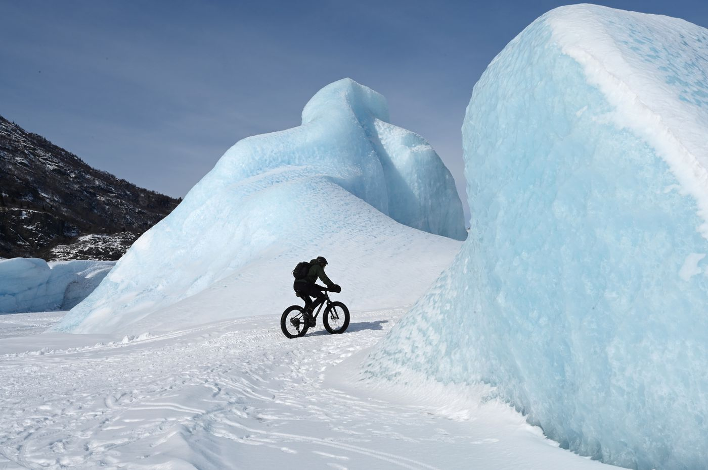 A biker pedals between two icebergs from Knik Glacier on Wednesday, March 24, 2021. (Anne Raup / ADN)