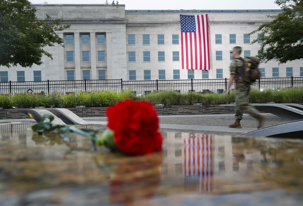 A member of the military walks the grounds of the National 9/11 Pentagon Memorial before the start of the September 11th Pentagon Memorial Observance at the Pentagon on the 17th anniversary of the September 11th attacks, Tuesday, Sept. 11, 2018. (AP Photo/Pablo Martinez Monsivais)