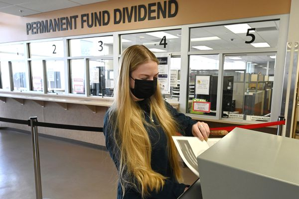 Julia Cox placed her Permanent Fund Dividend application in a secure drop box inside the Anchorage PFD office at 655 F Street in the Linny Pacillo parking garage on Tuesday, March 30, 2021. The deadline for filing for a 2021 Alaska Permanent Fund dividend online is 11:59 p.m. on Wednesday, March 31. Dividend information offices in Anchorage, Fairbanks, and Juneau are closed to the public, but the lobbies are open between 10 a.m. and 4 p.m. on Wednesday for residents to pick up and drop off PFD applications. (Bill Roth / ADN)
