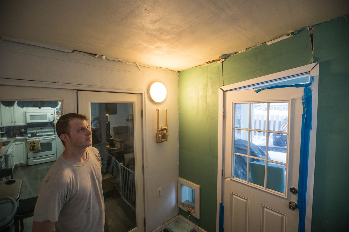 Matthew Robison stands in his earthquake-damaged Jewel Lake home on Dec. 28. Nearly a dozen homes in his cul-de-sac were yellow-tagged, indicating significant damage after the Nov. 30 quake. (Loren Holmes / ADN archive)