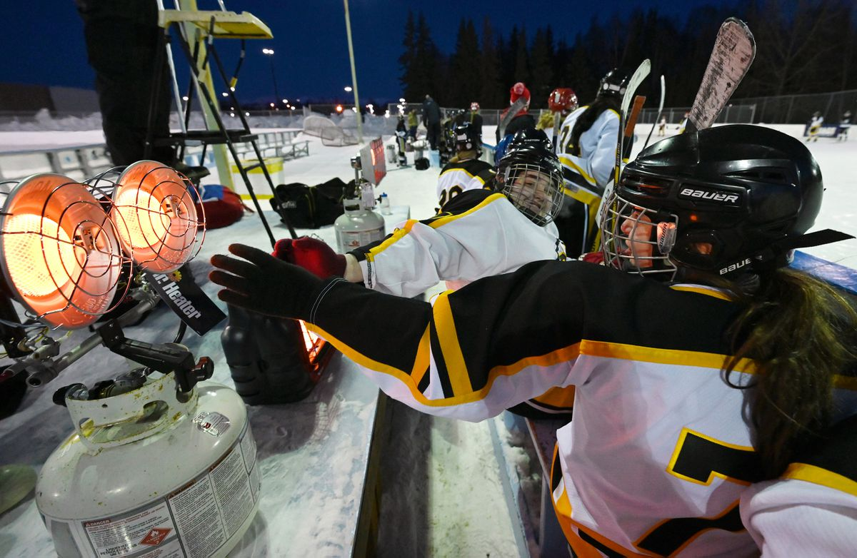 West High sophomore forward Kim Damrill and Dimond High freshman forward Makayla Reimers warm their hands next to a propane heater late in the third period at the Bonnie Cusack Outdoor Ice Rinks on Monday, Feb. 1, 2021. South/Bartlett defeated Dimond/West 2-0 in the first round of the girls high school hockey championships. The round-robin outdoor tournament continues Wednesday and Friday, with the third-place game and title tilt are set for Saturday. (Bill Roth / ADN)