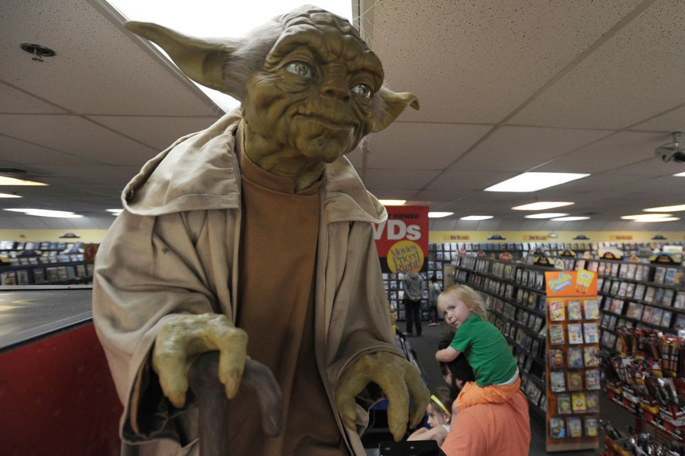 Charlie Johnson, 2, looks up at Yoda while riding on his father Matt Johnson's shoulders at the DeBarr Road Blockbuster on Monday with his sister Amelia. (Bill Roth / Alaska Dispatch News)