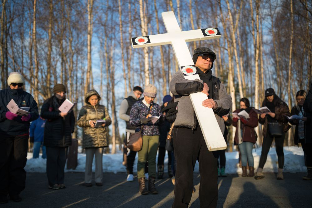 Basilio Garcia carries a cross during a Good Friday faith walk from Our Lady of Guadalupe parish to town square on Friday. Catholic faithful from across Anchorage participated in the walk, commemorating the crucifixion of Jesus Christ. (Loren Holmes / ADN)