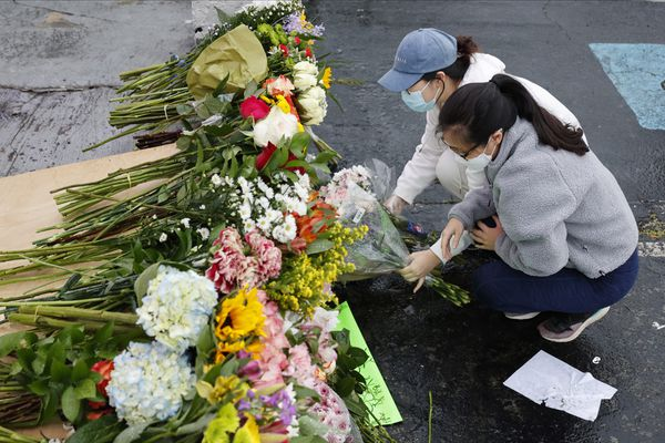 Jenny Choi, left, and Kristi You place flowers at the entrance of Gold Spa, one of three Atlanta-area locations where deadly shootings happened this week. Six of the eight people killed were Asian women. MUST CREDIT: Photo by Chris Aluka Berry for The Washington Post