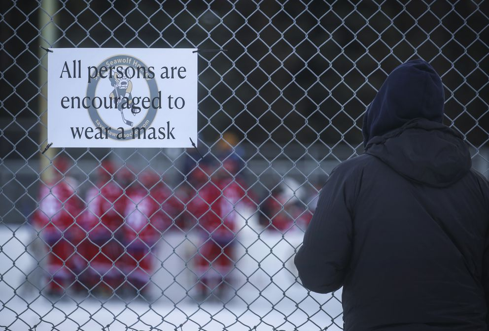 A spectator stands along the fence during a timeout on the ice at the Bonnie Cusack Outdoor Ice Rink in Anchorage on Thursday, Jan. 21, 2021. (Emily Mesner / ADN)