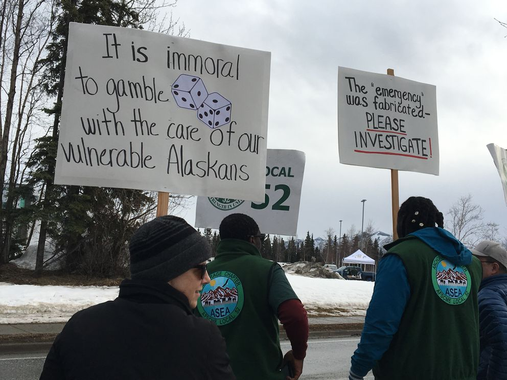 Protesters line up along Piper Street on Saturday, March 23, 2019 brandishing signs opposing the move to privatize the Alaska Psychiatric Institute. (Madeline McGee / ADN.)