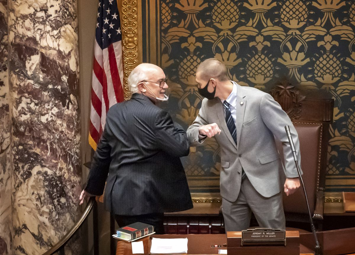 FILE - In this Nov. 12, 2020 file photo, outgoing Minnesota State Senate President Senate President Jeremy Miller, R-Winona gave Sen. David Tomassoni, DFL-Chisholm a congratulatory elbow bump before Tomassoni addressed the Senate Chamber in St. Paul, Minn. At least 187 state legislators nationwide have tested positive for the virus and four have died since the pandemic began, according to figures compiled by The Associated Press. . (Glen Stubbe/Star Tribune via AP)