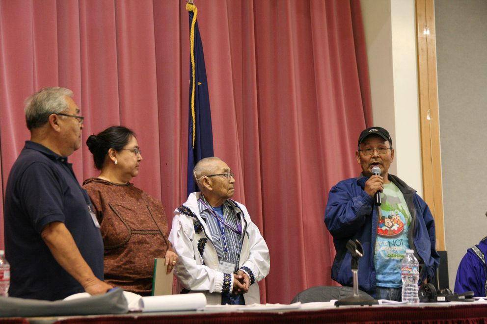 Association of Village Council Presidents chairman Henry Hunter, on the left, new chief executive Vivian Korthuis, and traditional chief Peter Moore listen on Thursday, Oct. 6, 2016, as former longtime president Myron Naneng thanks tribal members for allowing him to serve. His playful Disney T shirt shows he is on vacation now, he said. (Lisa Demer / Alaska Dispatch News)