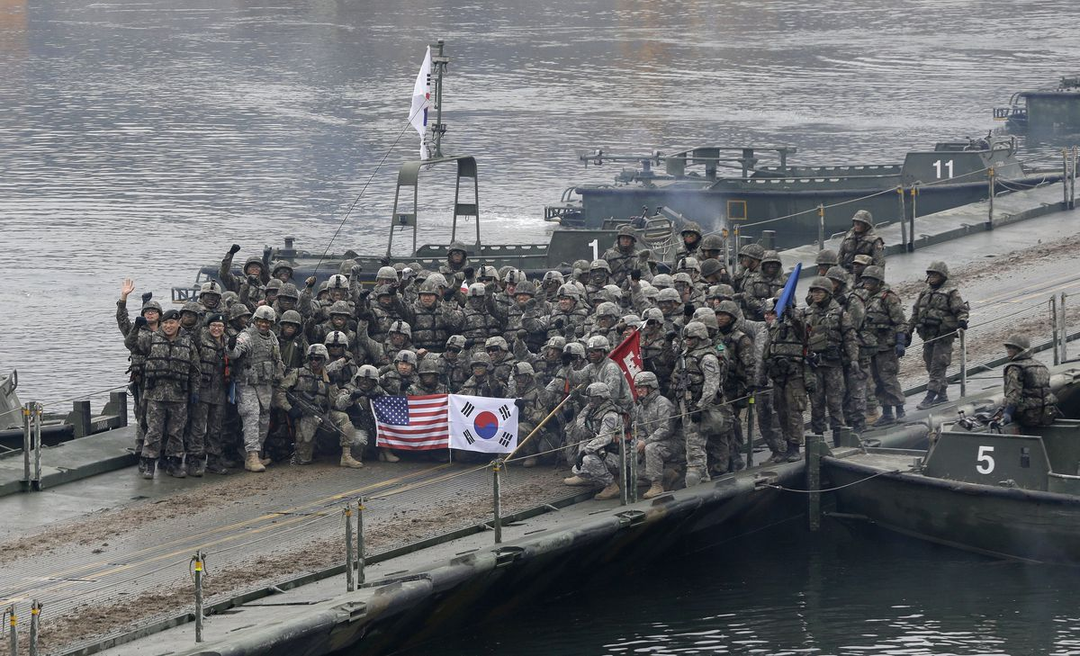 FILE - In this Dec. 10, 2015, file photo, U.S. and South Korean army soldiers pose on a floating bridge on the Hantan river after a river crossing operation, part of an annual joint military exercise between South Korea and the United States in Yeoncheon, south of the demilitarized zone that divides the two Koreas, South Korea. (AP Photo/Ahn Young-joon, File)