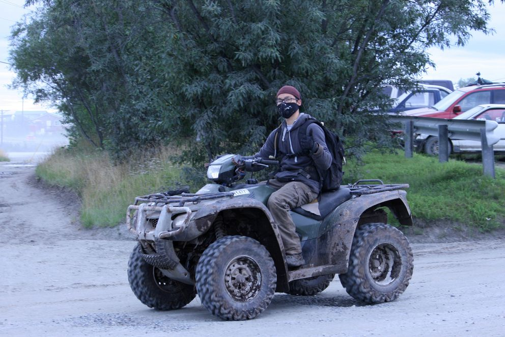 A driver on a four-wheeler protects his face from the dust in Bethel. (Lisa Demer / Alaska Dispatch News)