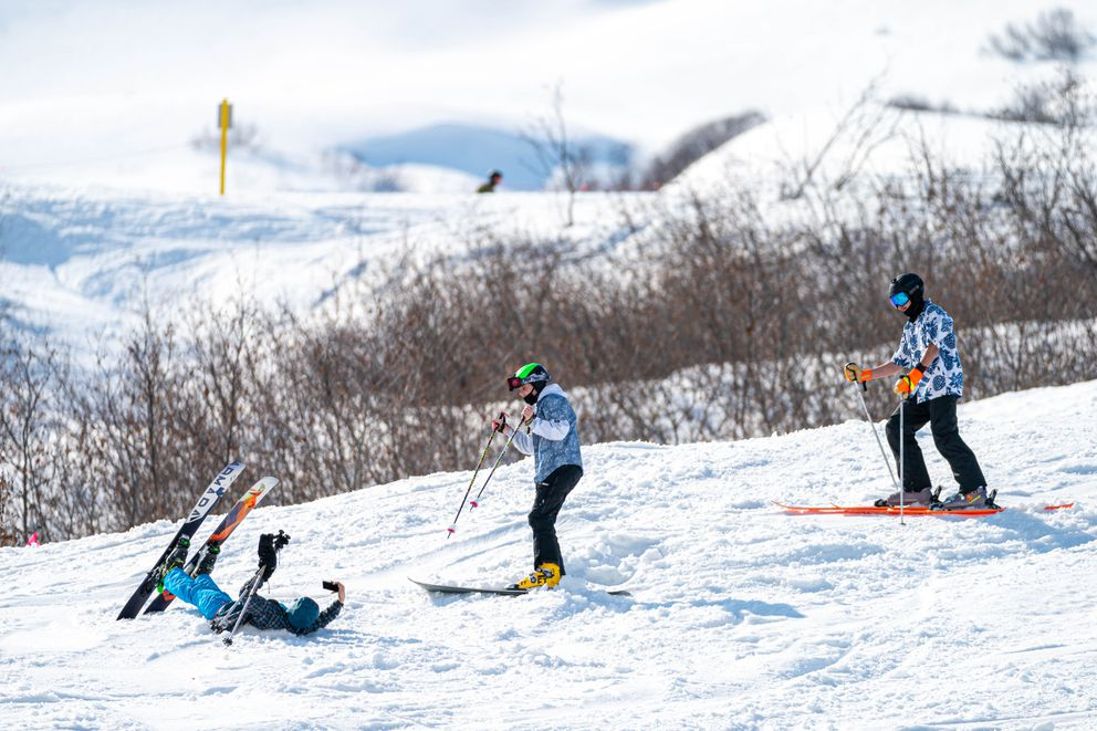 A skier lies down in the snow to take a photo of their companions on Friday, April 16, 2021 at Skeetawk in Hatcher Pass. This weekend is the ski area's final weekend for skiing and riding, although it will be open on April 24 and 25 for a fat bike race fundraiser. (Loren Holmes / ADN)