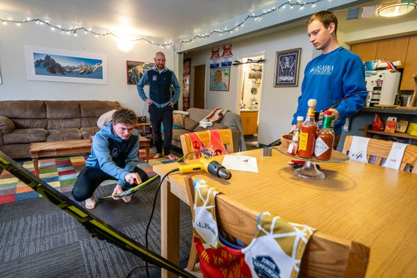 "From left, Alaska Pacific University skiers Kai Meyers, Forrest Mahlen, and Hunter Wonders wax skis with klister in their home on Thursday, April 16, 2020 on the APU campus. The skiers are some of about a half dozen that chose to ""hunker down"" together during the coronavirus pandemic. (Loren Holmes / ADN)"