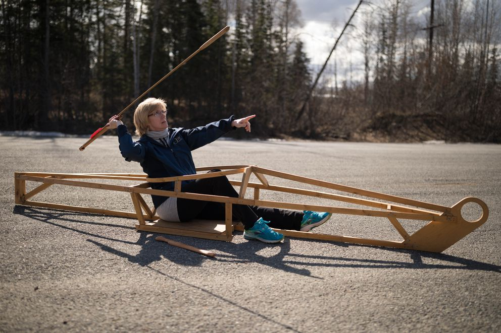 Cindy Palmatier tries to hit a target with a spear thrown from a kayak shell. (Loren Holmes / Alaska Dispatch News)