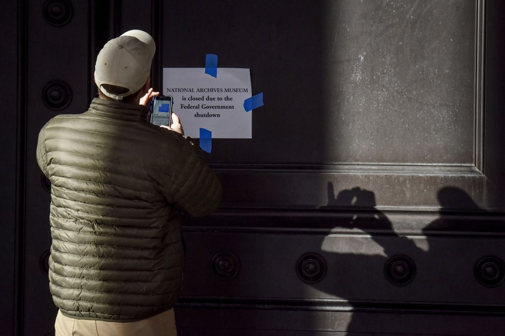 A man takes a photograph of a closed sign on the entrance to the National Archives museum in Washington, D.C., on Saturday. (Washington Post photo by Jahi Chikwendiu)