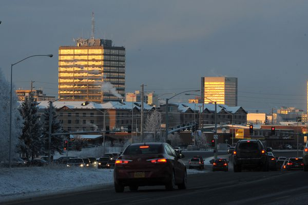 The setting sun reflects off buildings in Midtown Anchorage as traffic on the Seward Highway approaches a red light at 36th Avenue on Thursday, Dec. 28, 2017. (Bill Roth / ADN)