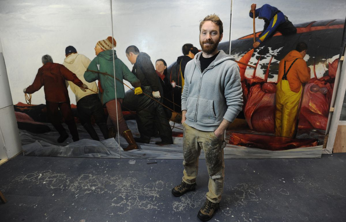 """Artist David Pettibone with his """"The Whaleas a Dish, Spring Hunt,"""" one of two large-scale triptych paintings of subsistence whale hunting in Utqiagvik. (Bill Roth / Alaska Dispatch News)"""