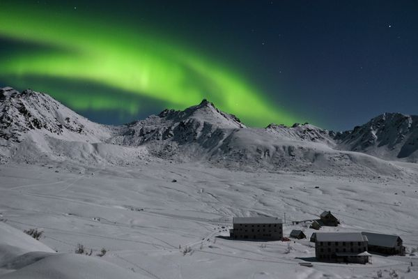 The northern lights arc over the ridges in this view from Hatcher Pass state recreation area on on Sunday, February 1, 2015. The historic buildings of Independence Mine are at bottom right. (Marc Lester / ADN archive)