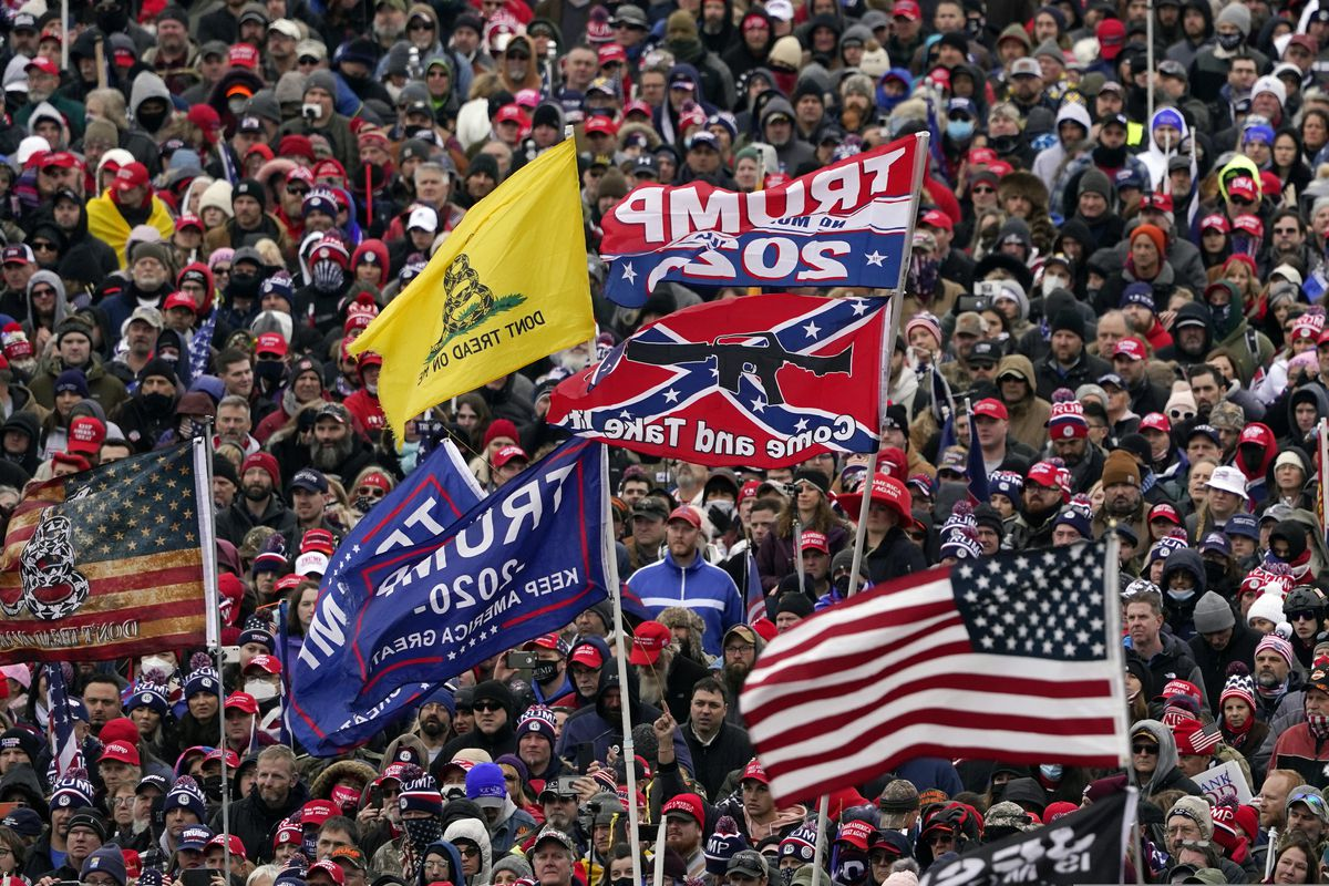 FILE In this Wednesday, Jan. 6, 2021, file photo, supporters listen as President Donald Trump speaks as a Confederate-themed and other flags flutter in the wind during a rally in Washington. War-like imagery has begun to take hold in mainstream Republican political circles in the wake of the deadly attack on the U.S. Capitol, with some elected officials and party leaders rejecting calls to tone down their rhetoric contemplating a second civil war. (AP Photo/Evan Vucci, File)