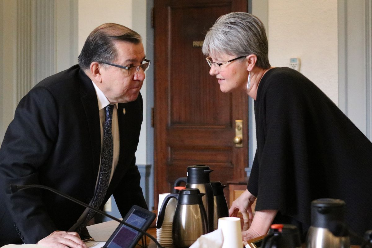Alaska state Sens. Lyman Hoffman, D-Bethel and Anna MacKinnon, R-Eagle River, chat during a break from a Senate Finance Committee hearing Thursday. The two senators are co-chairs of the committee, which released a batch of budget proposals at the hearing. (Nathaniel Herz / ADN)