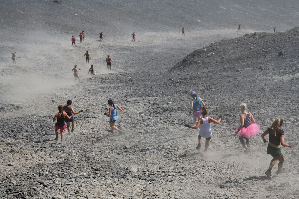 Racers kick up dust as they descend during the Mount Marathon women's race on July 4, 2019, in Seward. (Marc Lester / ADN)
