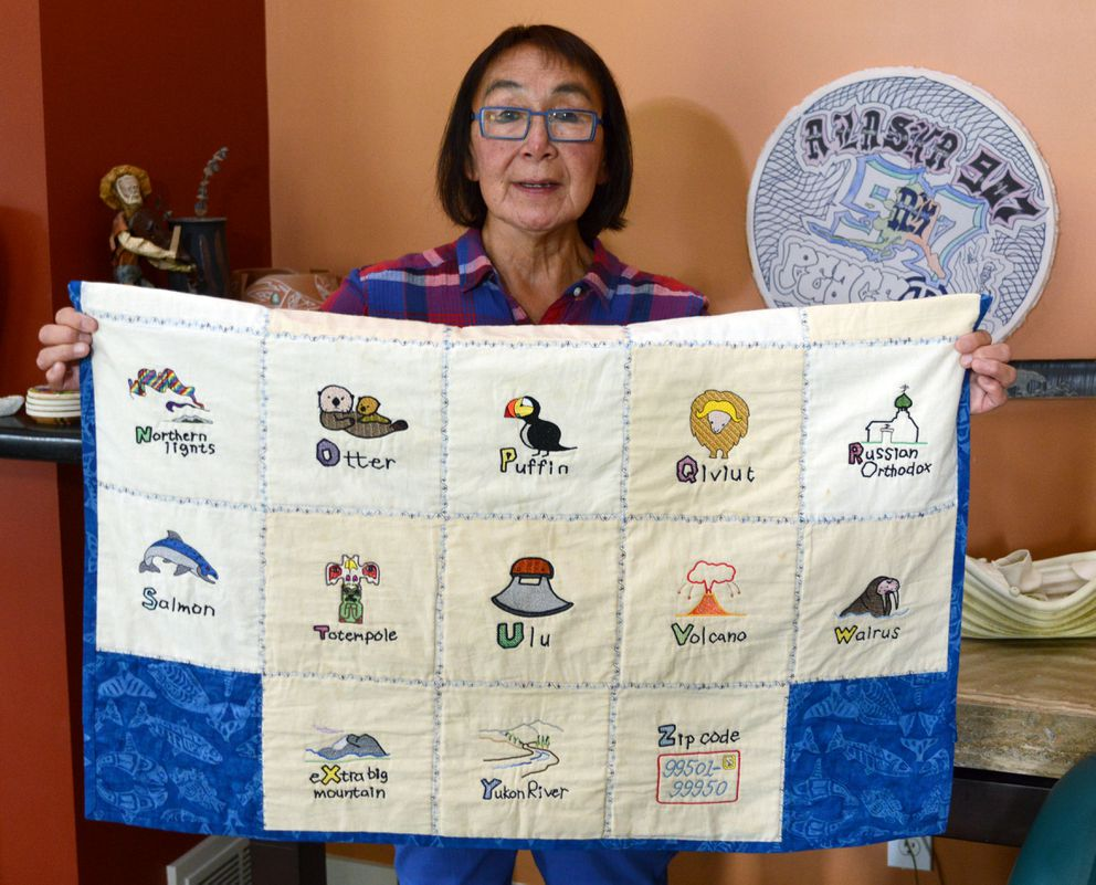 An alphabet quilt was presented to Jenny Alowa upon her retirement from a 25-year teaching career at McLaughlin Youth Center. The drum at back was made by a former student. (Erik Hill / Alaska Dispatch News)