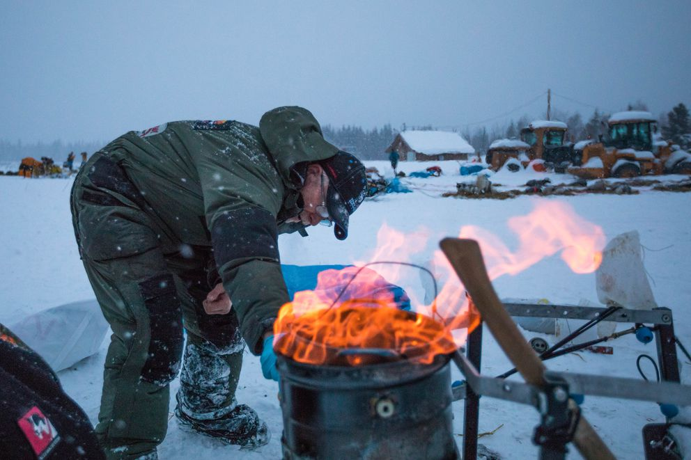 Jeff King cleans his cooker at the Nikolai checkpoint on Tuesday, March 6, 2018 during the Iditarod Trail Sled Dog Race. (Loren Holmes / ADN)