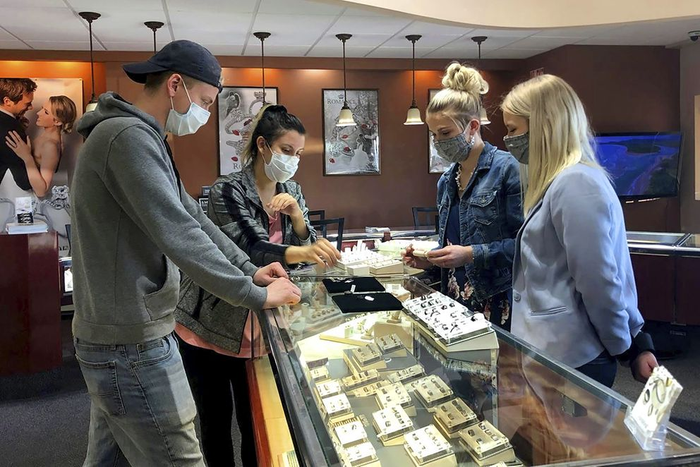 This photo from KTVF-TV sows a couple picking out their wedding bands at Bishops Jewelry Gallery in Fairbanks, Alaska, on Friday, April 22, 2020. (Sara Tewksbury/KTVF-TV via AP)