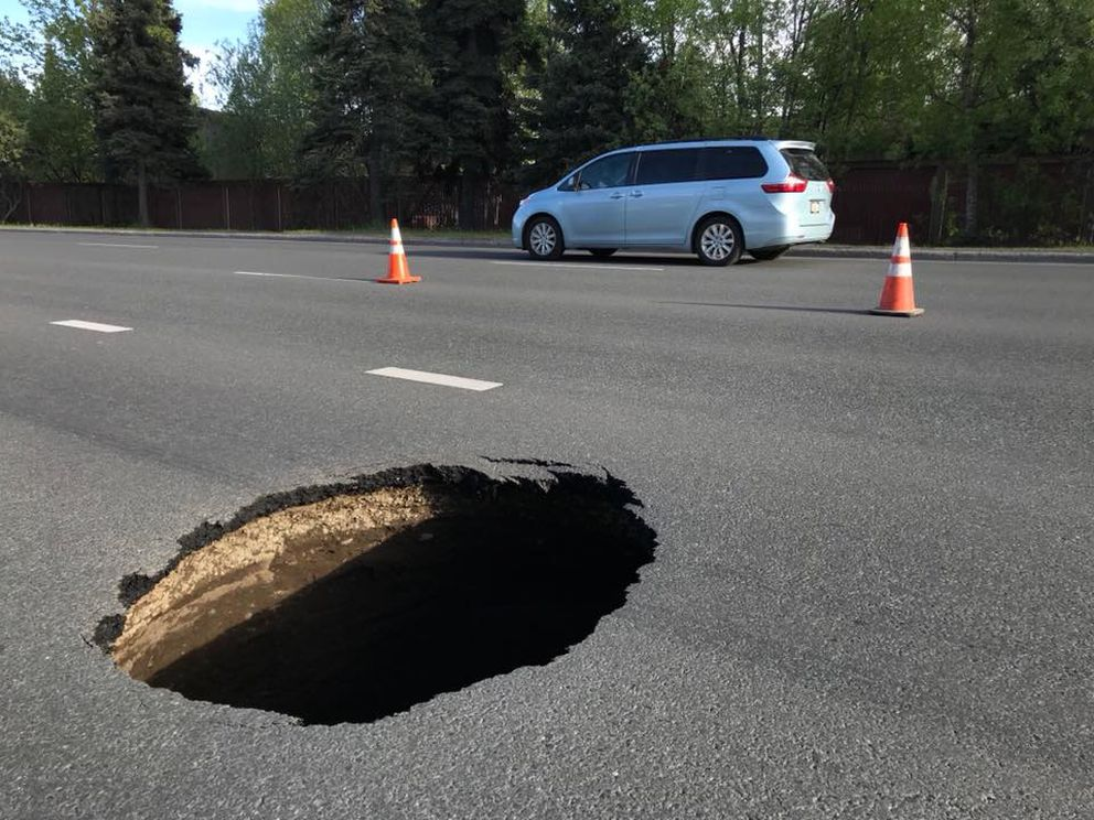 A sinkhole that appeared on West Benson Boulevard in Anchorage in May 2018 was traced to a rotting steel drain pipe below from the 1980s. (Bill Roth / ADN)
