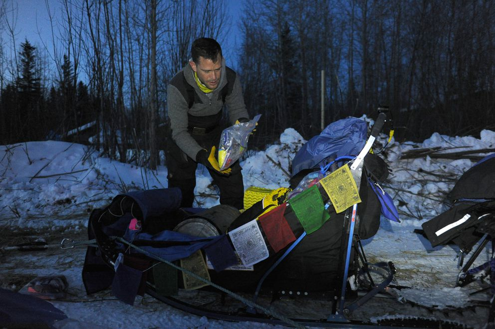 Larry Daugherty packs his sled bag in preparation to leave the village of Tanana during the 2017 Iditarod. (Bob Hallinen / ADN)