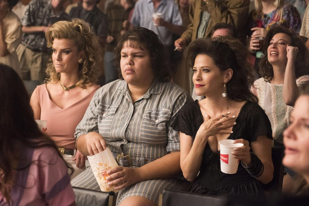 "Betty Gilpin, left, Chugiak High School alum Britney Young, center, and Jacki Tohn watch a wrestling match in the Netflix series ""GLOW."" (Erica Parise / Netflix)"